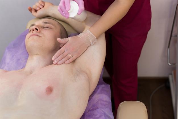 Косметолог наносит дезинфицирующий раствор на подмышки мужчины перед процедурой депиляции сахарной пастой.