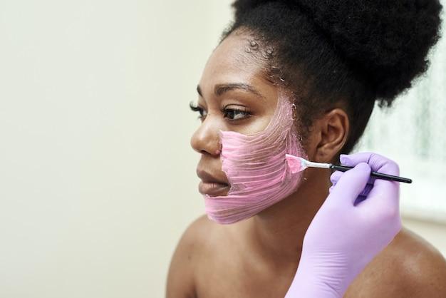미용사는 고객의 얼굴에 보습 마스크를 바릅니다.