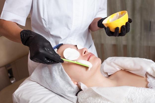 Косметолог накладывает на клиента альгинитовую маску.