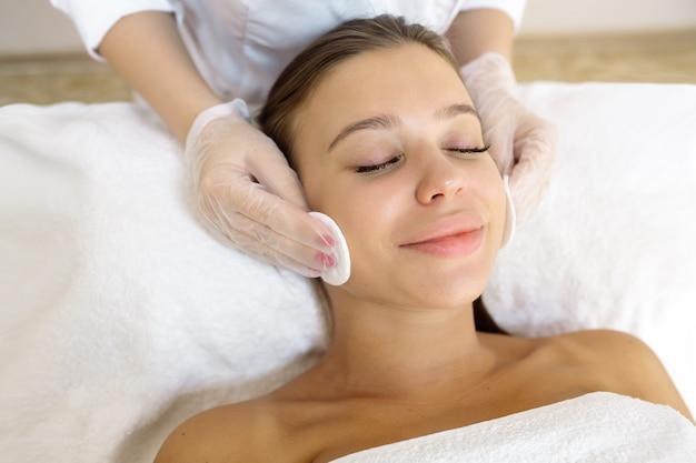 美容師は、手順の前に患者の顔を掃除します
