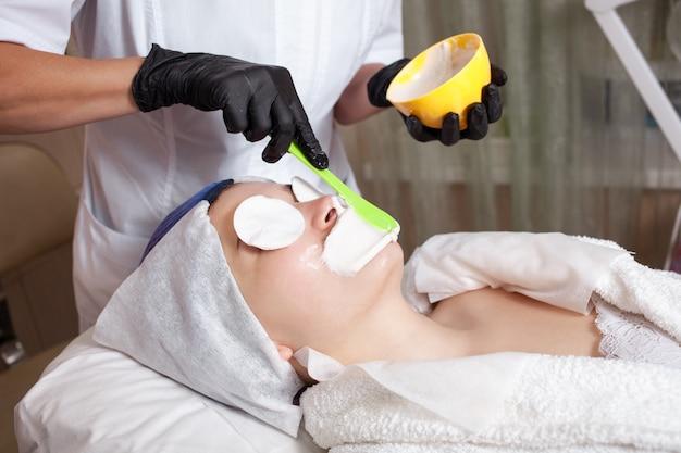 Косметолог делает маску в салоне красоты.