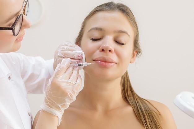 Косметолог делает пациенту увеличение губ с помощью инъекций наполнителя гиалуроновой кислоты.