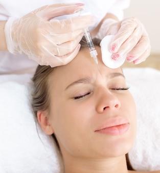 Косметолог делает пациенту коррекцию морщин ботоксом в области лба и между бровями.