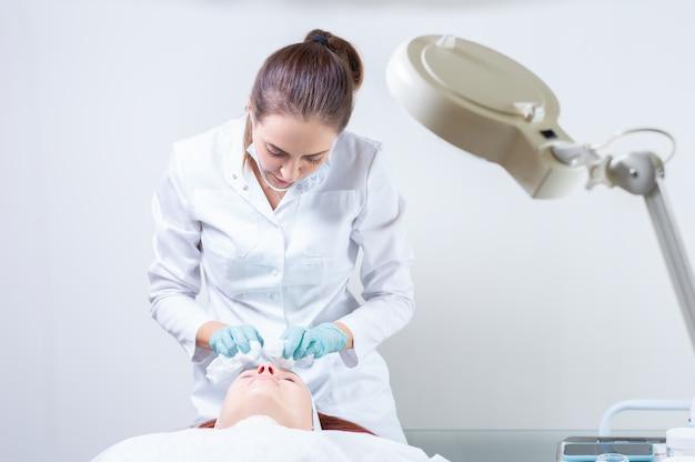Косметолог умывает лицо пациента перед пилингом. концепция ухода за кожей. смешанная техника