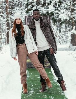 美しいアフリカ系アメリカ人のカップルとスタイリッシュな服を着た夏と緑の草を背景に冬の森でヨーロッパの外観の女の子。冬の夏のコンセプト。