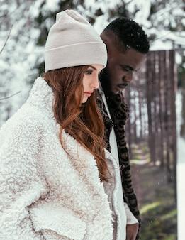 美しいアフリカ系アメリカ人のカップルとスタイリッシュな服を着て夏を背景に冬の森でヨーロッパの外観の女の子。冬の夏のコンセプト。