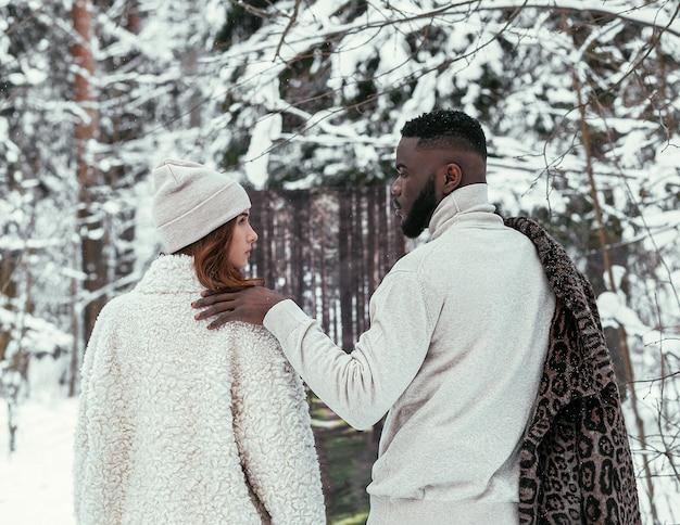 아름 다운 아프리카 계 미국인 부부와 세련 된 옷을 입고 여름 배경에 겨울 숲에서 유럽 모습의 소녀. 겨울 여름의 개념.