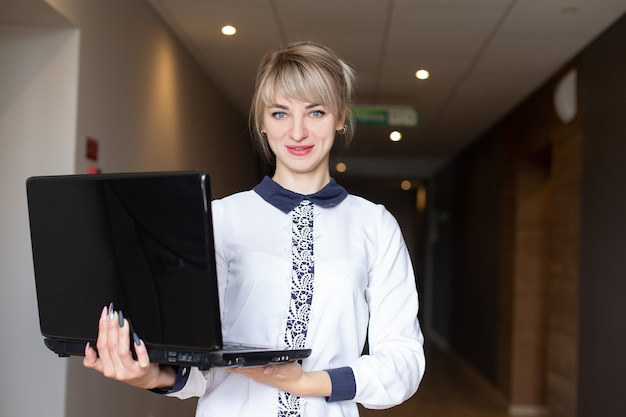 ノートパソコンの手に美しく幸せなブロンド