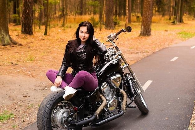 Красивая и счастливая брюнетка на мотоцикле