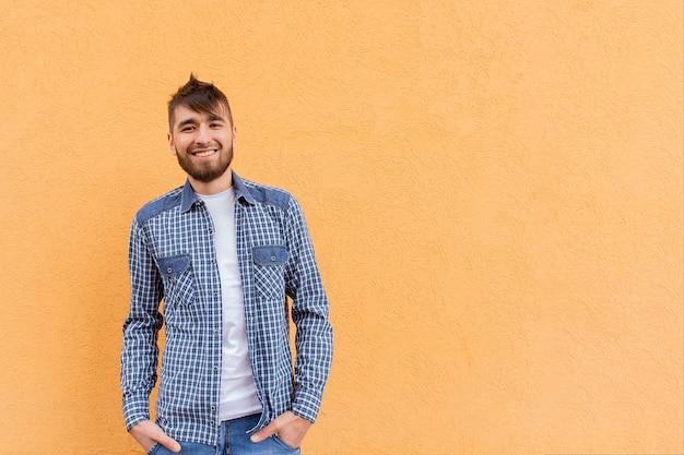 Красивый и счастливый мужчина у оранжевой стены