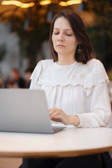美しく若いヨーロッパの女性は、コーヒーショップや公共の場所で彼女のラップトップで働いています Premium写真