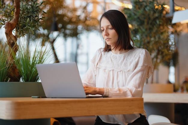 美しく若いヨーロッパの女性は、コーヒーショップや公共の場所で彼女のラップトップで働いています