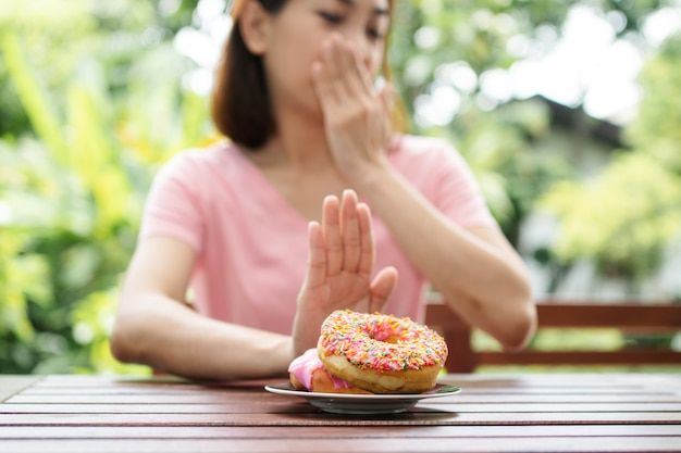 아름다운 아시아 건강한 중년 여성이 정원 옆에 발코니에 앉아 너트를 먹는 것을 거부합니다.