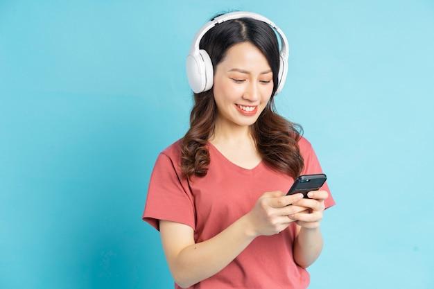 美しいアジアの女性は白いワイヤレスヘッドフォンで音楽を聴きながら電気を使用しています