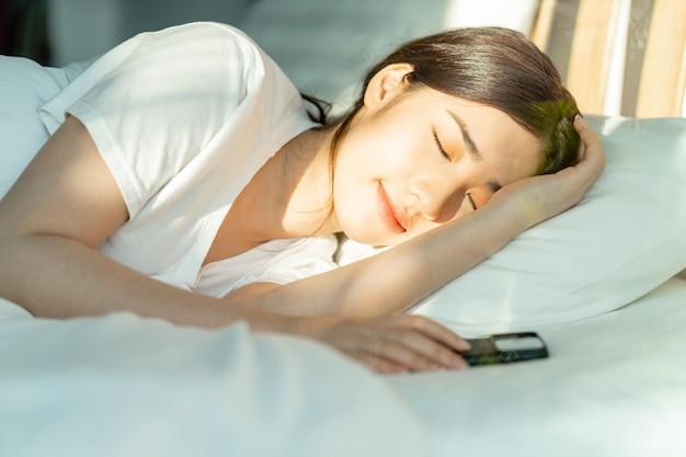 美しいアジア人女性は正午過ぎに携帯電話を横に置いて寝ていた