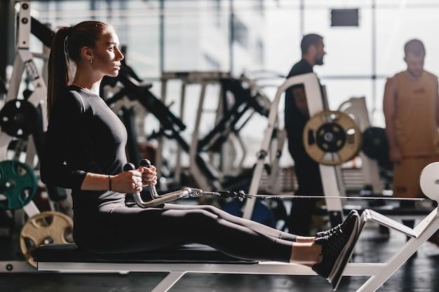 黒のスポーツウェアに身を包んだ美しい運動少女は、現代のジムのベンチで機器を使ってスポーツエクササイズをしています。