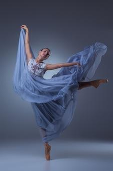 파란색 배경에 긴 파란색 드레스를 입고 춤추는 아름다운 발레리나