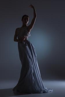 짙은 파란색 배경에 긴 파란색 드레스를 입고 춤추는 아름다운 발레리나