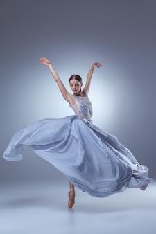 ライラックの背景に長いライラックのドレスで踊る美しいバレリーナ