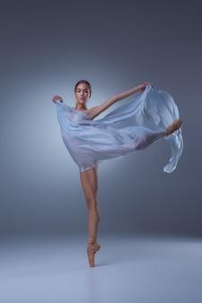 青い背景に青いベールで踊る美しいバレリーナ