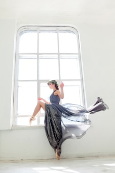긴 회색 드레스를 입고 포즈를 취하는 아름다운 발레리나
