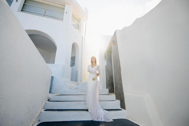 ギリシャのサントリーニ島の結婚式の白い長いセクシーなドレスで美しいブロンドの髪の若い女性の花嫁ブルー