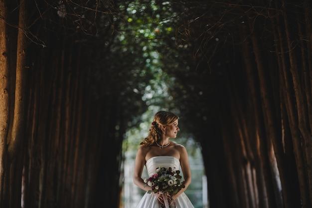 公園に花束のある美しい花嫁が立っています