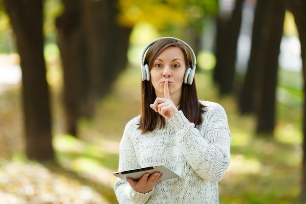 Красивая шатенка в белом свитере с планшетом приложила палец к губам, прося тишины в белых наушниках в осеннем парке в теплый день. осень в городе.