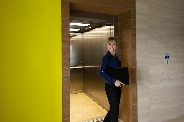 사무실에서 엘리베이터에서 나오는 아름다운 비즈니스 금발