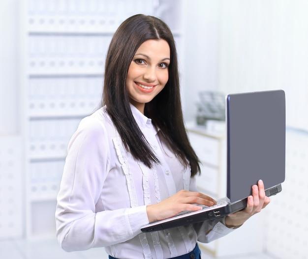 オフィスでコンピューターを持つ美しいビジネスウーマン
