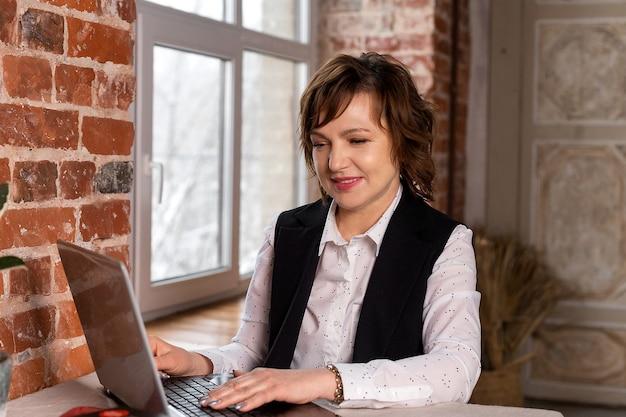 美しく、ビジネスライクな、成熟した女性は彼女のラップトップで働いています。ビジネスウーマン。