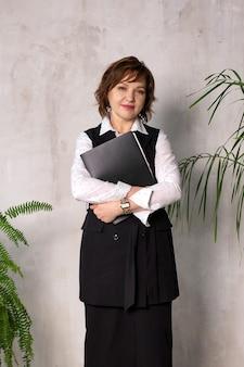 美しく、ビジネスライクで、成功した、成熟した女性は、彼女の手にフォルダーを持って立っています
