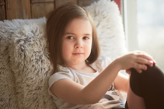 The beautiful child sitting on the window sill