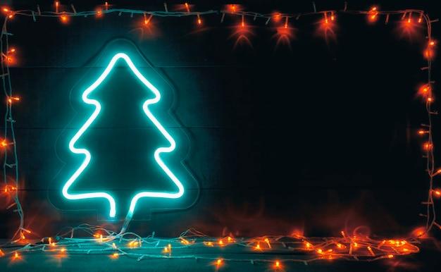 나무 책상에 조명과 흰색 네온 크리스마스 트리가 많은 아름다운 크리스마스 배경