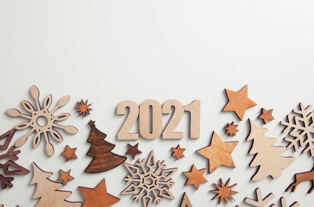 Красивый новогодний фон с множеством маленьких деревянных украшений и деревянных цифр 2021 на белом столе.
