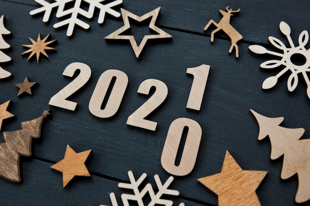 木製の机の上に小さな木製の装飾と木製の番号2021がたくさんある美しいクリスマスの背景。