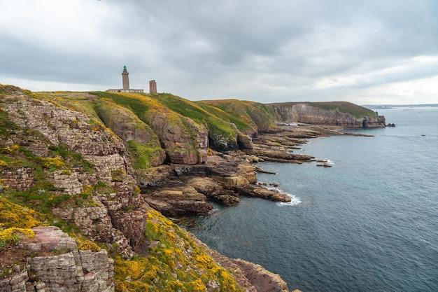 Красивое побережье рядом с phare du cap frehel - это морской маяк в кот-д'армор (франция). на вершине мыса фрехеля