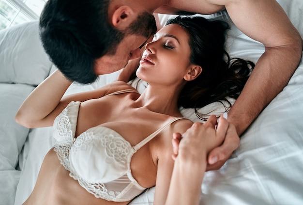 ベッドでキスする下着姿の美しいカップル