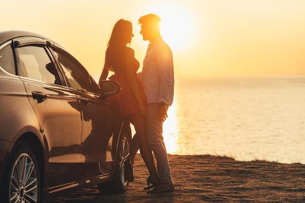 바다 해안에 차 근처에 서 있는 아름다운 커플