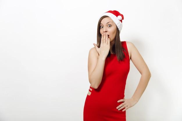 赤いドレスと白い背景の手で彼女の口を覆うクリスマスの帽子を身に着けている魅力的な笑顔を持つ美しいヨーロッパの若い幸せな女性。孤立したサンタの女の子。 2018年の年末年始のコンセプト