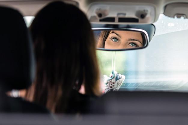 Красивые глаза молодой женщины-водителя отражаются в зеркале заднего вида.