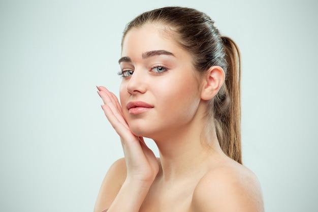 Красивое женское лицо. идеальная и чистая кожа лица на сером