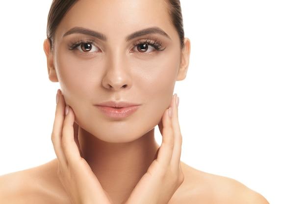 아름다운 여성의 얼굴. 흰 벽에 얼굴의 완벽하고 깨끗한 피부. 아름다움, 관리, 피부, 치료, 건강, 스파, 화장품 개념