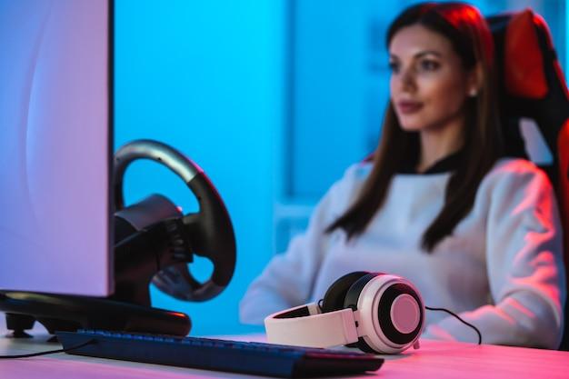 Красивая девушка-геймер с наушниками играет в видеоигры