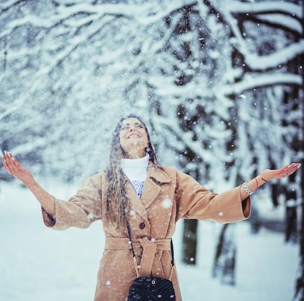 Красивая девушка играет со снегом