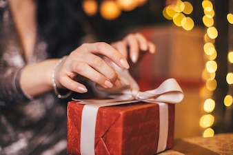 The beautiful girl sits on the floor and opens a present
