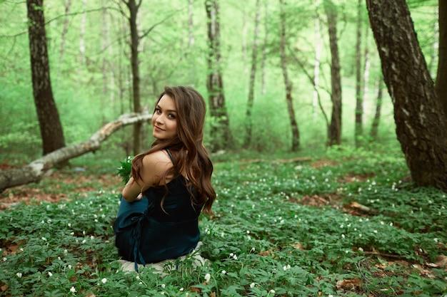 Красивая девушка, сидящая на земле