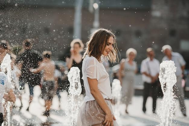 Красивая девушка, идущая возле фонтана