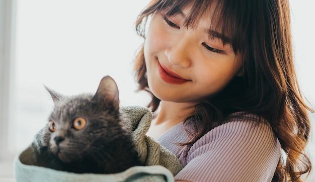 아름다운 소녀는 그녀의 고양이 털을 말리고 있었다