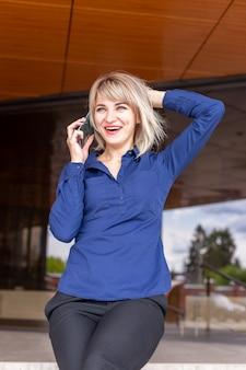 電話で話している美しい幸せなブロンド